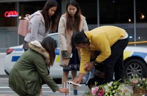 مشيّعون يضعون الورود ويشعلون الشموع في النصب التذكاري المؤقت بالقرب من مسجد النورفي نيوزيلندا