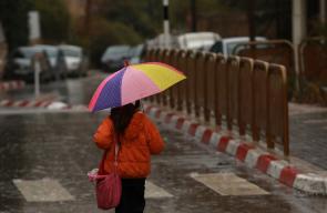 مواطنون يسيرون وسط مدينة نابلس خلال تساقط جيد للأمطار