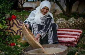 حاجة فلسطينية تستخدم (الجاروشة) في تنقية وطحن الحبوب