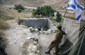 مواطنون يسبحون في عين فرعا المهددة بالمصادرة من قبل الاحتلال، في اذنا قرب الخليل