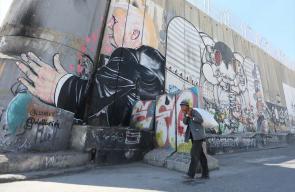 رسام بريطاني يظهر  ترامب وهو يعاتق الجدار الفاصل بمدينة بيت لحم