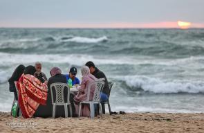 غزة ..فلسطينيون يتناولون طعام الافطار خلال شهر رمضان على شاطئ البحر