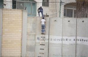 شبان يتسلقون جدار الفصل للتوجه إلى المسجد الأقصى المبارك في القدس لأداء صلاة الجمعة