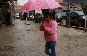 مواطنون يسيرون في مركز مدينة نابلس شمال الضفة الغربية، وسط أحوال جوية ماطرة