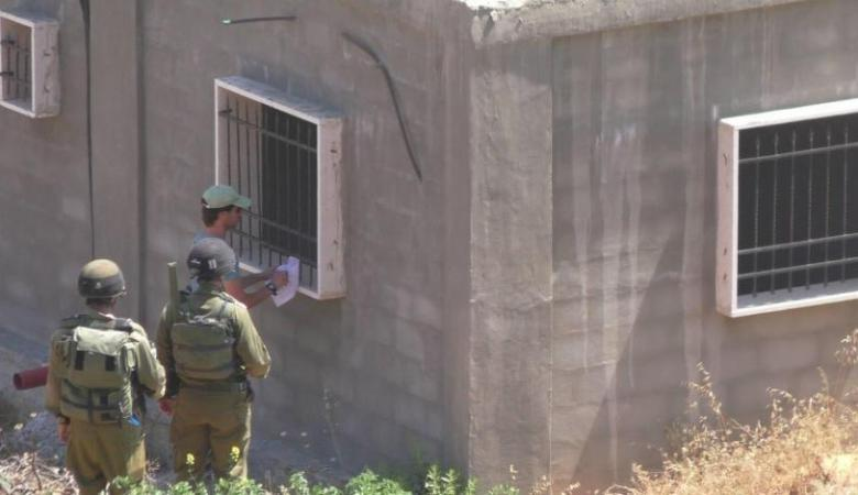 الاحتلال يستدعي مواطنين ويخطر بوقف البناء في جدران استنادية في الولجة