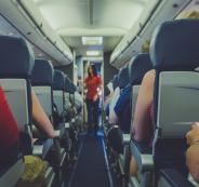 رجل يقف في ممر الطائرة لأجل زوجته