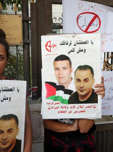 البيرة - فلسطينيون يغلقون مقر الصليب الاحمر تضامنا مع الاسير المضرب عن الطعام بلال كايد