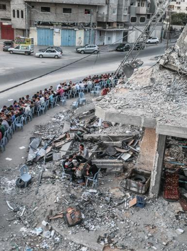 فلسطينيون يفطرون على  ركام برج دمره الاحتلال في العداون الاخير على غزة