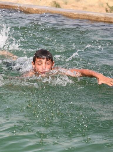 مواطنون واطفال يهربون من موجة الحر للسباحة في مدينة دورا جنوب الخليل